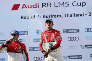 Alex  celebrates on the podium with champagne .