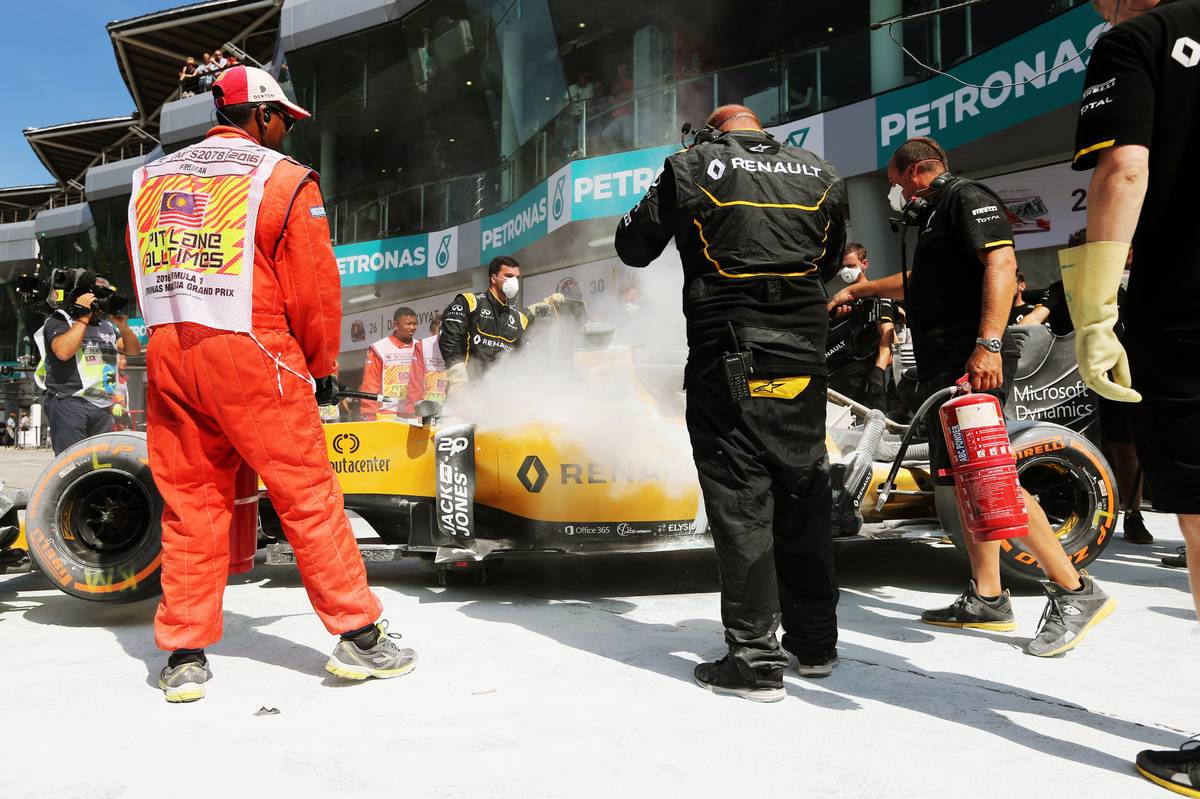 The Renault Sport F1 Team RS16 of Kevin Magnussen (DEN) is tended to by marshals and mechanics after it caught fire in the pits in the first practice session.